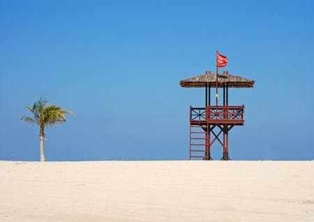 Red flag on the beach. A lifeguards hut ant palm tree. Stock Photo