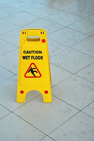 Caution wet floor sign stand on a ceramic surface