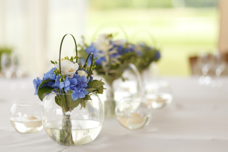 Wedding decoration of blue and white flowers in the round glass vase