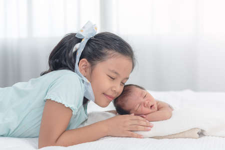 Sister happy welcome her little brother. Toddler kid meeting new sibling. Cute girl and new born baby boy relax in a white bedroom. Family with children at home.