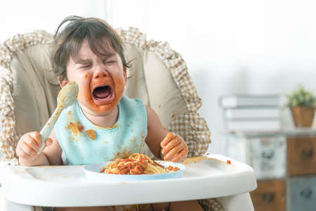 Lovely baby girl crying while eating spaghetti and making a mess. Family leave baby alone, eating pasta herself.