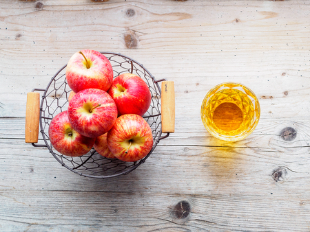 Apples in a wire basket and a glass of apple juice