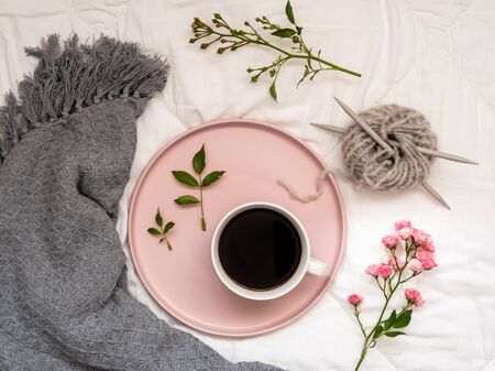 Breakfast in bed with a cup of coffee and flowers