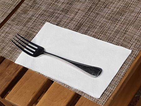 Spoon and knife on napery, table cloth mat on wood dining table in restaurant of hotel.