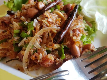 Fried Nham Salad, sour pork, Thai hot spicy food with chillis and green lettuce vegetables in a dish. Stock Photo