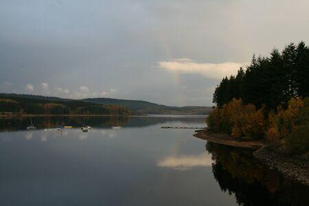 Rainbow reflected in lake photo