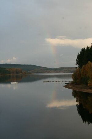 Rainbow reflection in lake photo