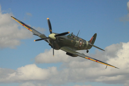 Spitfire in cloudy sky Stock Photo