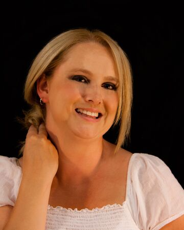 a young blonde woman smiling against a blac background