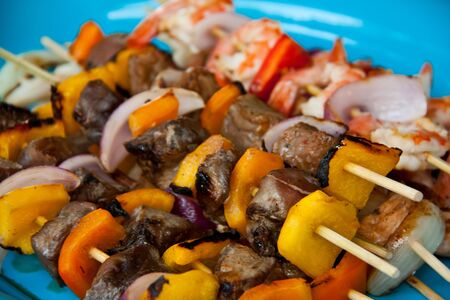 Beef, shrimp, and chicken skewers on a blue plate Stock Photo