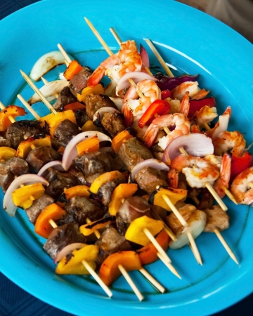 Beef, Shrimp, and Chicken skewers on a blue plate