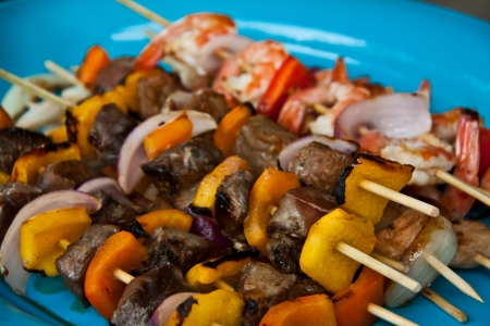 Beef, shrimp, and chicken skewers on a blue plate Фото со стока
