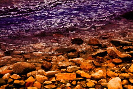 a rocky lakeshore in purple and gold