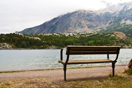 an empty bench at a mountain lake