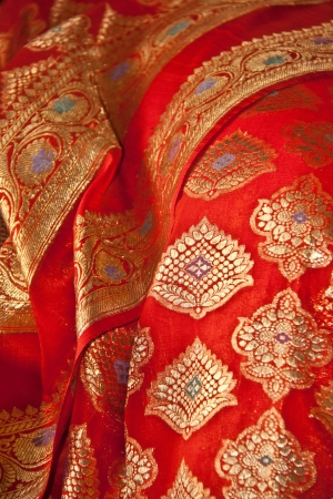 an Indian Sari with orange fabric and Gold thread