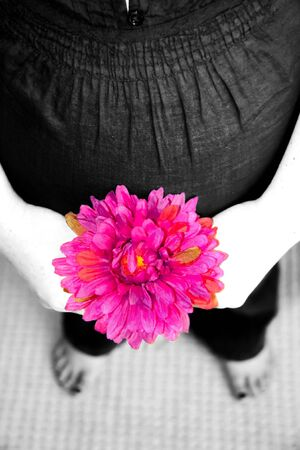 A pregnant woman in black and white with pink flower