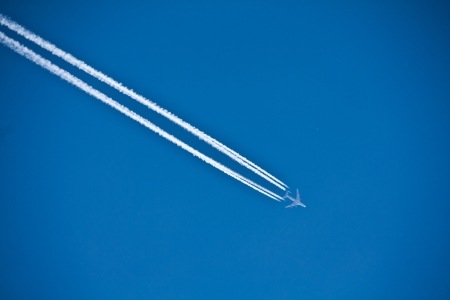 an airplane on a blue sky with vapor trails photo