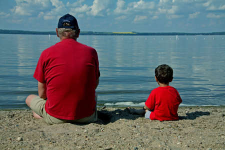 a man and a boy in red shirts on the beach at a lake