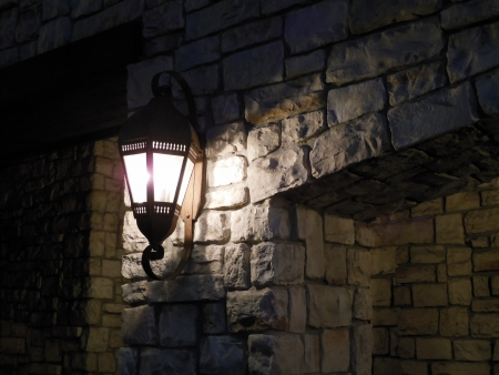 a lantern lit on a stone wall