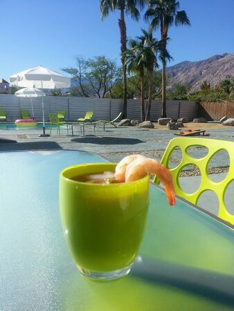 Poolside with a cocktail in Palm Springs, California on a sunny day.