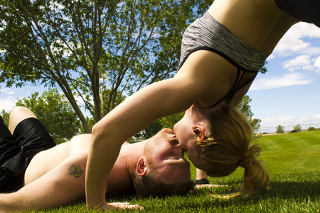 lats: A man laying on the grass kissing a woman doing a back bend.