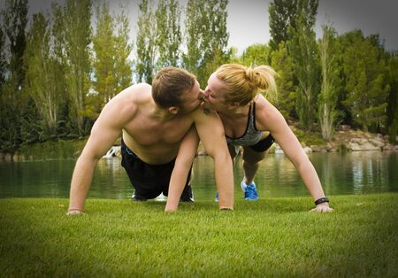back to back couple: A man and woman holding the plank position of a pushup while kissing each other.