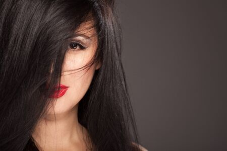 Beautiful brunette model. Half face covered with a bang. Red lipstick.