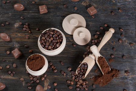 Ground coffee and coffee beans in a wooden bowl on the vintage wooden background.