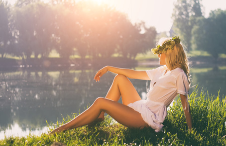 Beautiful model, slim blonde has a rest on a background of sunrise on the river. White dress, wreath of wild spring flowers. Air baths. Healthy lifestyle concept.