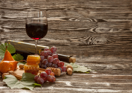 glass of red wine, honeycomb, grapes and pears on wooden background