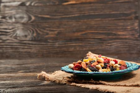 Dried fruits. Hazelnuts, almonds, cashews, apricots, cherries, walnuts, raisins. Background - Turkish plate and burlap. Vintage.