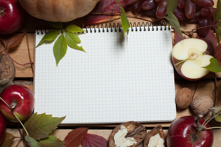Notebook with empty space for text, framed with autumn fruits: grapes, pumpkins, apples, walnuts. Book for recipes.
