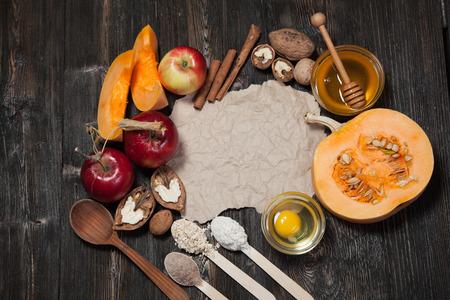Ingredients for pumpkin and apple pie. Apples, nuts, pumpkin, honey, flour, eggs, oatmeal, sugar on vintage wooden background. Imagens
