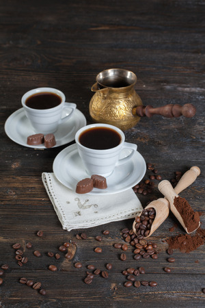 Fresh coffee cups, Turk. Ground coffee, crackers and coffee beans in a wooden bowl on the vintage wooden background. Imagens