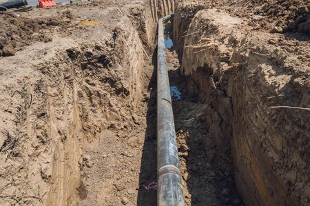Construction site of an underground oil and gas pipeline.Work of burying oil and gas supply pipeline.work on the pipe laying of the pipelines in a special corrosion-resistant insulation in the trench