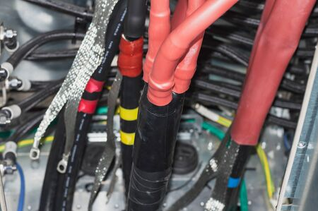 Electrician near the low-voltage cabinet. Uninterrupted power supply. Electricity.Three phase power transformer connection low voltage side.Instalando terminales para cable de gran potencia Banco de Imagens