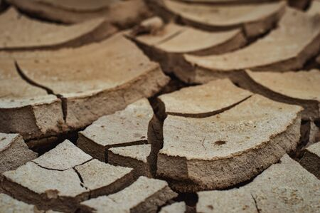 Natural Drought concept:Dried cracked earth soil ground texture background.desert rough land dry crack erosion in the ground due to drought.Dry red clay soil texture, natural floor background