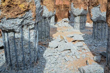 A construction worker cuts a concrete bored pile at piles cut off level.Construction of pile foundation. Steel bar structure concrete pile for of building foundation construction site. Banco de Imagens