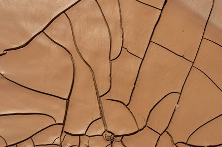 Natural Drought concept:Dried cracked earth soil ground texture background.desert rough land dry crack erosion in the ground due to drought.Dry red clay soil texture, natural floor background Banco de Imagens - 142694404