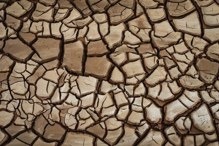 Natural Drought concept:Dried cracked earth soil ground texture background.desert rough land dry crack erosion in the ground due to drought.Dry red clay soil texture, natural floor background Banco de Imagens - 143113916