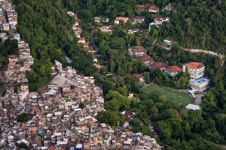 An aerial view over the favela of Rocinha alongside an expensive private school showing the wealth gap and income inequality of Rio de Janeiro, Brazil, where the poor and rich live side by side. Reklamní fotografie
