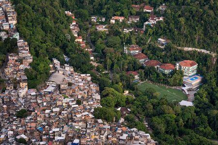Eine Luftaufnahme über die Favela von Rocinha neben einer teuren Privatschule, die das Wohlstandsgefälle und die Einkommensungleichheit von Rio de Janeiro, Brasilien, zeigt, wo Arme und Reiche Seite an Seite leben. Standard-Bild
