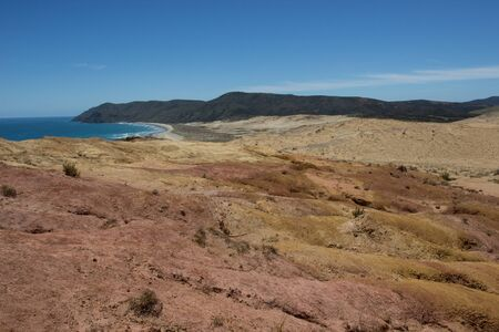 The moon-like colored clay hills of the New Zealands Cape Reinga in Northland, and Te Werahi Beach Stock Photo - 136910510