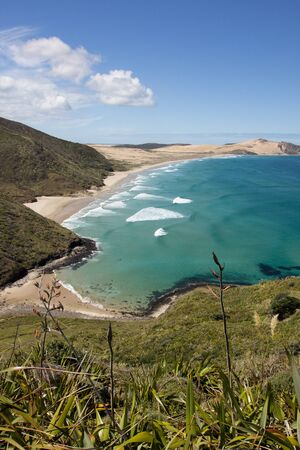 Blue surf of Te Werahi Beach and Cape Maria Van Diemen on the Cape Reinga in Northland, New Zealand.