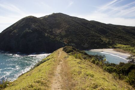 The seaside mountain ridge of the Te Paki Coastal trail around Cape Reinga in Northland, New Zealand. The hiking trail is on a grass covered hill, with the small secluded Sandy Bay and mountains.