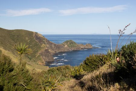 Rocky bays of the Cape Reinga coastline at the northern tip of New Zealand. The sea and seaside mountains are viewed from the Te Paki Coastal Track, a four day hiking trail in Northland. Stock Photo - 136910578