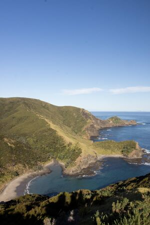 A sunny morning view from the Te Paki Coastal Track overlooking Sandy Bay in Northland, New Zealand. An aerial view of the small coves and seaside mountains of the northern-most hiking track in NZ. Stock Photo - 136910579