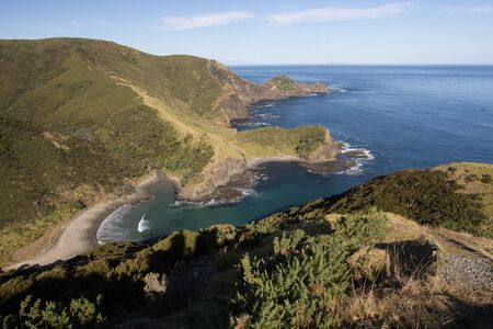 An aerial view of Sandy Bay as seen from the Te Paki Coastal Track, a 4 day hiking trail in Northland, New Zealand. Small rocky bays are scattered along the coastline with deep blue sea water.