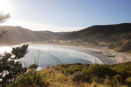 Tapotupotu Bay in the early morning light as seen from the Te Paki Coastal Track in Northland, New Zealand. Aerial photo taken from a grassy trail of the remote bay surrounded by mountains. Stock Photo