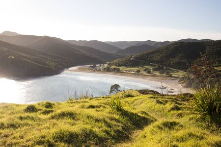 Early morning aerial view over Tapotupotu Bay in Northland, New Zealand, from the Te Paki Coastal Track. The hiking track leads over the grassy hill beside the pristine bay surrounded by mountains.